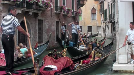 Gondolas-take-people-through-a-narrow-canal-with-buildings-on-each-side-in-Venice-Italy