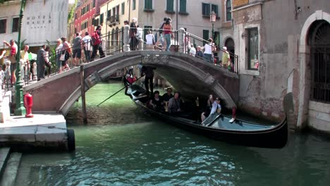 Gondolas-take-people-through-a-narrow-canal-with-buildings-on-each-side-in-Venice-Italy-1