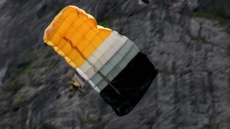 A-man-paraglides-through-a-mountain-pass-near-a-waterfall