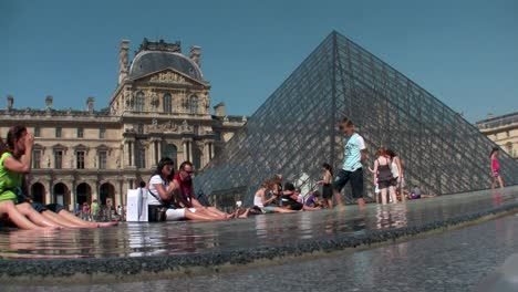 People-sit-in-front-of-the-Louvre-in-Paris