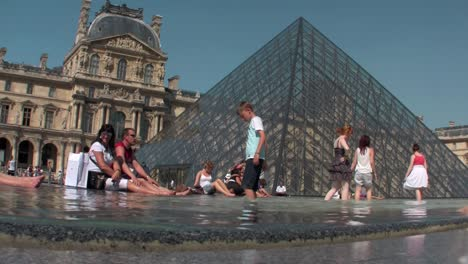 People-sit-in-front-of-the-Louvre-in-Paris-1