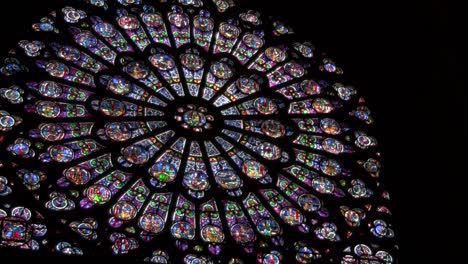 A-round-stained-glass-window-in-a-darkened-cathedral
