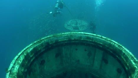 Divers-swim-around-a-shipwreck
