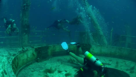 Divers-swim-around-a-shipwreck-1