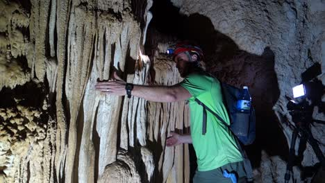 A-man-in-a-cave-plays-stalactites-like-a-musical-instrument