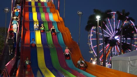 Children-ride-a-large-colorful-slide-next-to-a-Ferris-Wheel-at-night