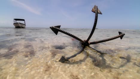 Close-up-of-anchor-at-low-tide-with-boat