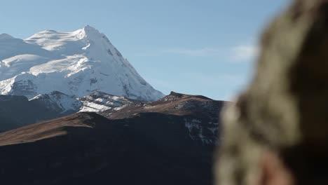 Pan-from-behind-rock-revealing-snowy-peak