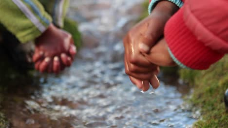 Close-up-of-children-s-hands-in-brook