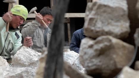 Slow-pan-of-stone-masons-chiseling