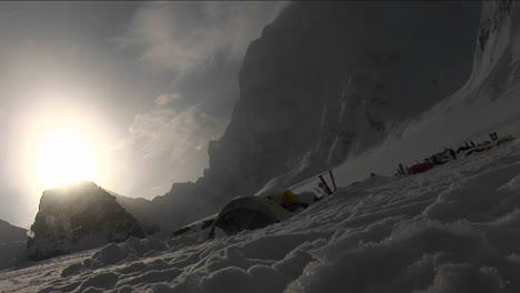 Snow-falling-through-sun-onto-camp