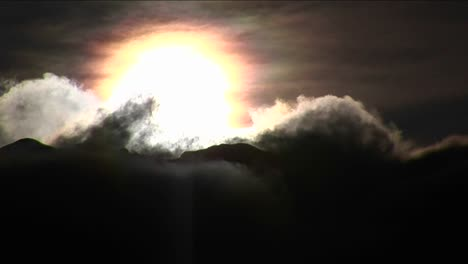 Clouds-moving-above-mountains-and-sun