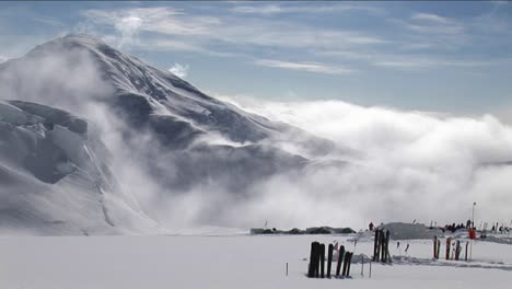 Skis-in-the-snow-as-the-wind-blows-over-peak