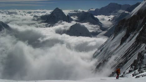 Climber-crossing-with-clouds-and-cliff-in-back