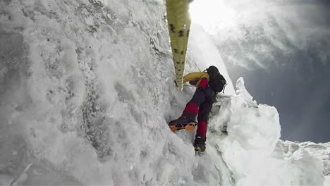 Climber-on-icy-wall-with-wind-and-snow-blowing