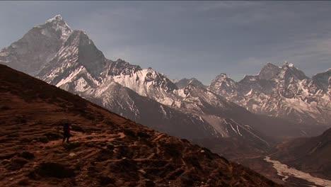 Trekker-headed-down-trail-peaks-in-background