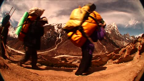Fish-eye-shot-of-porters-passing-by-on-trail-in-Himalayas