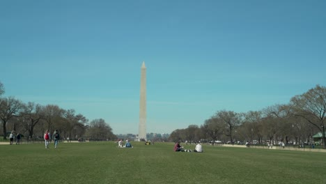 People-sit-on-the-mall-in-Washington-DC-with-Washington-Monument-background-on-a-spring-day