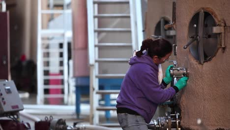 Telephoto-shot-of-a-female-winery-worker-checks-a-guage-on-a-stainless-steel-tank