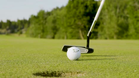 Slow-motion-close-up-of-a-putter-striking-a-golf-ball-and-sinking-a-short-putt