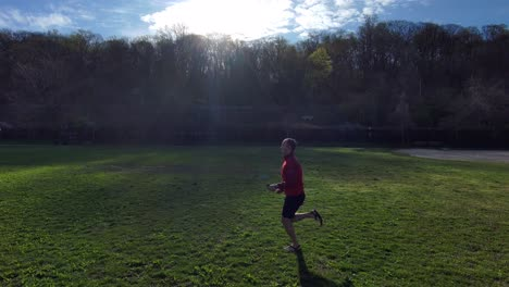 Aerial-of-a-man-running-near-a-forest-as-the-start-of-a-workout