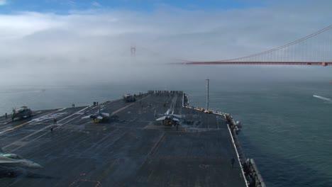 An-Aircraft-Carrier-Sails-Under-The-Golden-Gate-Bridge