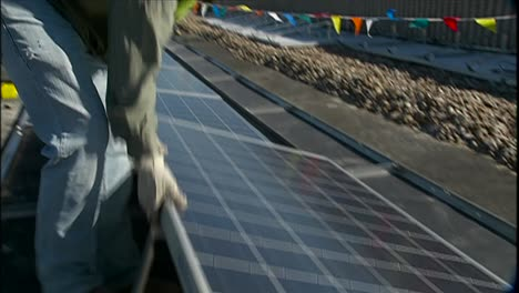 A-Crew-Installs-Solar-Panels-On-The-Roof-Of-A-Local-Business