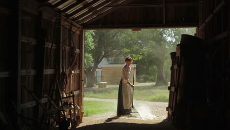 A-Farm-Woman-In-Traditional-Dress-Rakes-Out-A-Barn