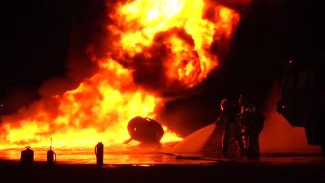 Bomberos-Con-Trajes-De-Materiales-Peligrosos-O-Resistentes-Al-Calor-Luchan-Contra-Un-Incendio-Intenso-Por-La-Noche-3