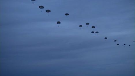 Varias-Vistas-Terrestres-De-Paracaidistas-Saltando-Desde-Aviones-Militares-Por-La-Noche