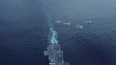 Us-Navy-Fighter-Jets-Fly-Over-An-Aircraft-Carrier