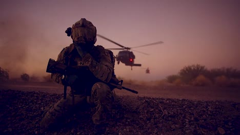 A-Soldier-Kneels-As-Helicopters-Land-On-A-Mission-Behind-Him