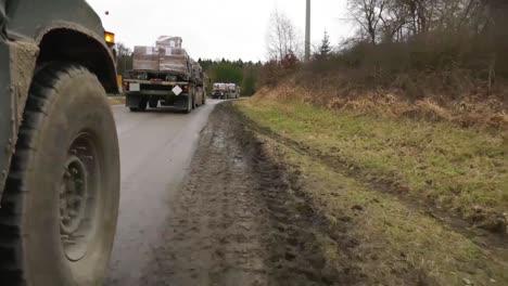 Un-Convoy-Del-Ejército-Estadounidense-De-Soldados-Y-Suministros-Se-Mueve-A-Lo-Largo-De-Una-Carretera-Embarrada-En-Alemania