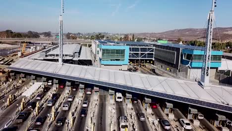 Steigende-Antenne-über-Dem-Grenzübergang-San-Ysidro-Tijuana-Us-Mexiko-Mit-Autos-Die-Kilometerweit-Aufgereiht-Sind