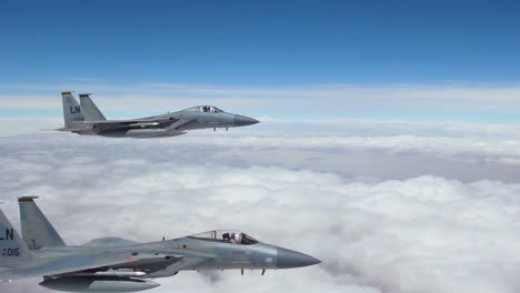 American-F15-Fighter-Jets-Fly-In-Formation-High-Above-The-Clouds-And-Then-Peel-Off