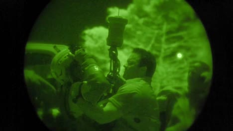 A-Military-Search-And-Rescue-Commando-Rescues-A-Civilian-Man-From-An-Emergency-Via-Rope-And-Helicopter-In-Night-Vision