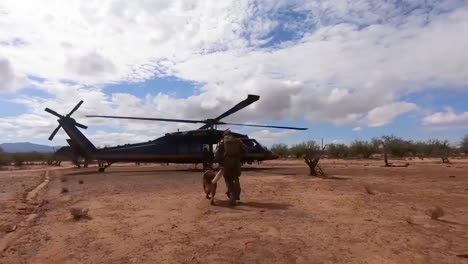 A-Member-Of-The-Us-Border-Patrol-Walks-The-Border-Between-The-Us-And-Mexico-With-A-Dog-Canine-And-Enters-A-Helicopter