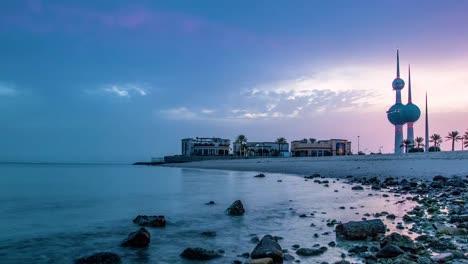Ein-Zeitraffer-Eines-Sonnenaufgangs-über-Einem-Strand-In-Kuwait-Mit-Dem-Wahrzeichen-Der-Kuwait-Türme-Im-Hintergrund
