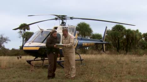 Ein-Polizeibeamter-Des-Wildlife-Refuge-Spricht-Mit-Einem-Hubschrauberpiloten-Und-Beobachtet-Wie-Sein-Flugzeug-Abhebt