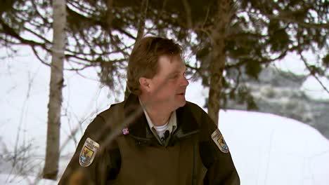 Ein-Beamter-Der-Schutzhütte-Durchquert-Eine-Winterliche-Landschaft-Auf-Schneeschuhen-Und-Einem-Schneemobil