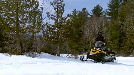 Ein-Polizist-Patrouilliert-Mit-Einem-Schneemobil-Durch-Einen-Wald-In-Vermont
