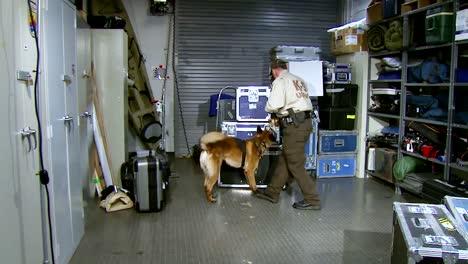 Ein-K9-Hund-Und-Sein-Offizier-Durchsuchen-Einen-Gepäckraum