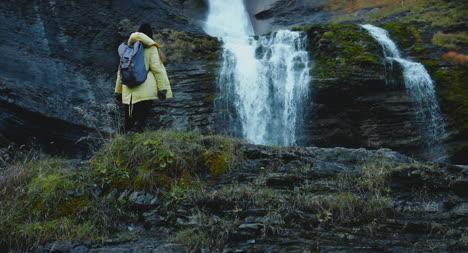 Climbing-Over-Rocks-Near-Waterfall-01