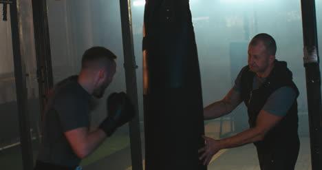 Saco-de-boxeo-hombre-boxeo-en-el-gimnasio-01