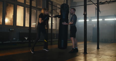 Woman-Boxing-Punching-Bag-with-Trainer