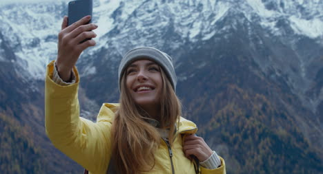 Woman-Taking-Selfie-In-Front-of-Mountains