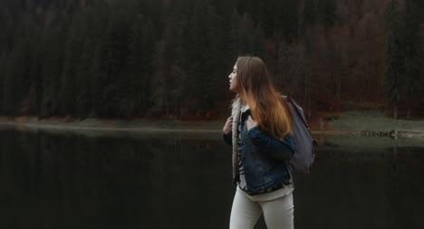Woman-Walking-Alongside-Lake-01