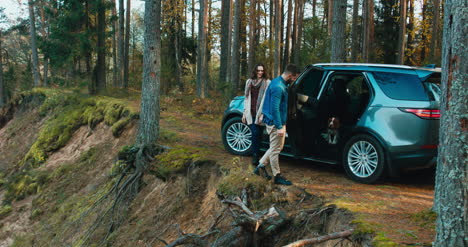 Couple-and-dog-exit-car-in-forest-4K