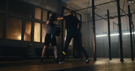 Woman-Boxing-with-Man-Holding-Pads