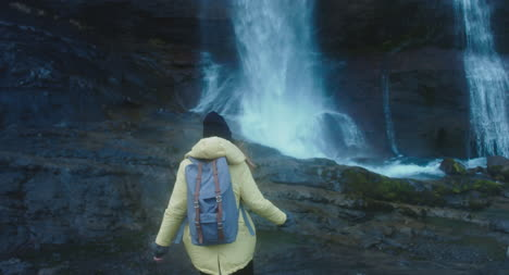 Woman-Hiking-Up-to-Waterfall